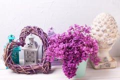Cuore decorativo, fiori lilla e lanterne del brigh sul wo bianco Fotografie Stock