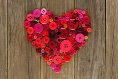 Cuore dei bottoni rossi e rosa su legno Fotografie Stock Libere da Diritti