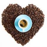 Cuore dei chicchi di caffè con la tazza blu azzurrata isolata sulla parte posteriore di bianco Fotografie Stock Libere da Diritti