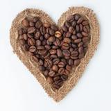 Cuore dei chicchi di caffè e della tela da imballaggio che si trovano su un fondo bianco Fotografia Stock