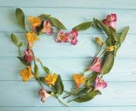 Cuore dei fiori che accolgono su un fondo di legno di alstroemeria Immagine Stock Libera da Diritti