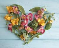 Cuore dei fiori su un fondo di legno di alstroemeria Immagini Stock