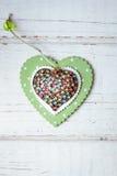 Cuore dei gioielli sopra il cuore di legno sopra i precedenti di legno Immagine Stock