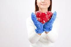 Cuore del biglietto di S. Valentino in mani delle ragazze Fotografie Stock