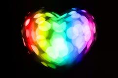 Cuore del bokeh dell'arcobaleno su fondo nero Fotografia Stock