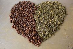 Cuore del caffè nero dei grani e delle foglie di tè verdi immagini stock