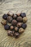 Cuore del cioccolato dai dolci su un fondo di legno Immagine Stock