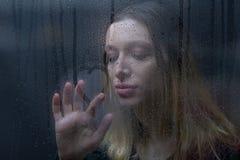 Cuore del disegno della donna sulla finestra nebbiosa il giorno piovoso Fotografie Stock