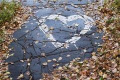 Cuore del disegno sulla pavimentazione Asciughi le foglie Percorso bagnato immagini stock