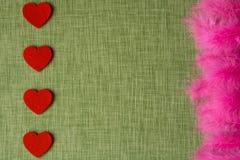 Cuore del feltro e piume di uccello tinte sul fondo del tessuto Fotografia Stock