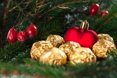 Cuore del giocattolo di Natale che sta dalla folla della caramella Pino verde e bacche rosse dell'agrifoglio sui precedenti Fotografia Stock