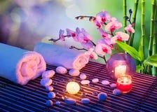 Cuore del massaggio delle pietre con le candele, orchidee