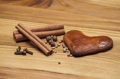 Cuore del pan di zenzero con le spezie sul bordo di legno Fotografia Stock