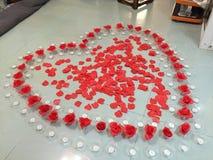 Cuore del petalo di Rosa con le candele Fotografia Stock