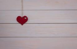 Cuore del ` s del biglietto di S. Valentino che appende sul cavo naturale Fondo bianco di legno Retro stile fotografia stock libera da diritti