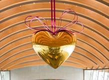 Cuore dell'oro che appende con il nastro porpora del metallo Fotografia Stock