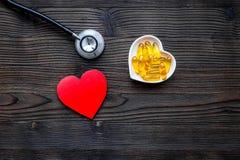 Cuore dell'ossequio Pillole in ciotola nella forma di cuore vicino allo stetoscopio sul copyspace di legno scuro di vista superio Fotografie Stock Libere da Diritti