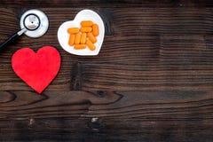 Cuore dell'ossequio Pillole in ciotola nella forma di cuore vicino allo stetoscopio sul copyspace di legno scuro di vista superio Fotografia Stock