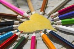 Cuore della foglia e primo piano colorato delle matite Fotografia Stock