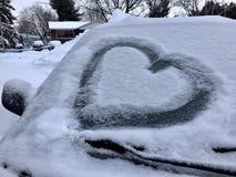 Cuore della neve sull'automobile ghiacciata Fotografia Stock