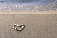 Cuore della pietra sulla sabbia Immagini Stock Libere da Diritti