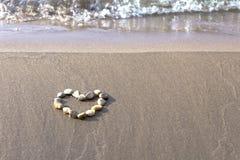 Cuore della pietra sulla sabbia Fotografie Stock
