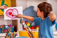 Cuore della pittura del bambino nella classe di scuola di arte Festa di giorno di madre Immagine Stock Libera da Diritti