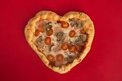 Cuore della pizza a forma di su rosso immagine stock