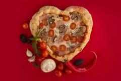 Cuore della pizza a forma di su rosso fotografia stock
