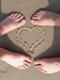 Cuore della sabbia con il piede degli amanti Fotografia Stock