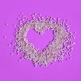 Cuore delle perle del bagno su un fondo rosa fotografie stock