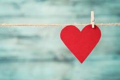 Cuore di carta che appende sulla corda contro il fondo di legno del turchese per il giorno di biglietti di S. Valentino fotografia stock