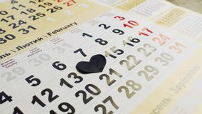 Cuore di carta nero sul il quattordicesimo febbraio su un calendario Amore e cuore rotto stock footage