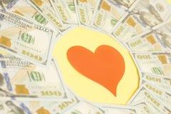 Cuore di carta rosso e cento banconote in dollari Immagine Stock