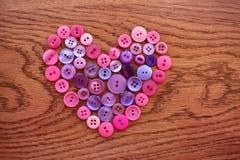 Cuore di cucito porpora e rosa del bottone su legno Fotografia Stock