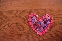 Cuore di cucito porpora e rosa del bottone su legno Immagini Stock Libere da Diritti