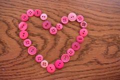 Cuore di cucito rosa del bottone su legno Immagini Stock Libere da Diritti