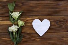 Cuore di legno bianco con i fiori su fondo marrone Giorno del biglietto di S Cartolina d'auguri nozze Immagini Stock Libere da Diritti