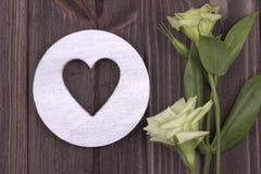 Cuore di legno bianco con i fiori su fondo scuro Giorno del biglietto di S Cartolina d'auguri nozze Immagini Stock