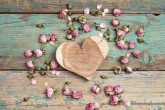 Cuore di legno con i fiori rosa secchi sul vecchio di legno del turchese fotografia stock