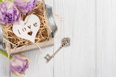 Cuore di legno in contenitore di regalo d'annata con i tulipani chiave e porpora Fotografia Stock