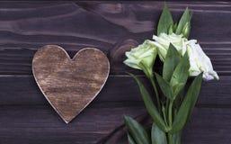 Cuore di legno di Brown con i fiori su fondo scuro Giorno del biglietto di S Cartolina d'auguri nozze Immagini Stock Libere da Diritti