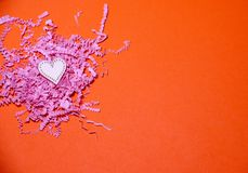 Cuore di legno sui precedenti di carta arancio con carta affettata rosa Fondo di giorno di biglietti di S. Valentino con i cuori  immagini stock libere da diritti