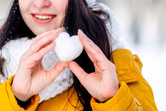 Cuore di neve nelle mani di una ragazza Immagini Stock
