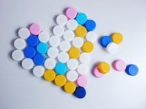 Cuore di plastica delle capsule di colore Fotografia Stock