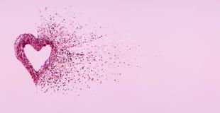 Cuore di scintillio che si dissolve nei pezzi su fondo rosa Giorno di biglietti di S. Valentino, cuore rotto e concetto di emerge immagini stock libere da diritti