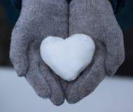 Cuore di Snowy in mani fotografia stock