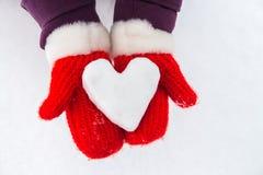 Cuore di Snowy in mani con i guanti rossi Immagine Stock