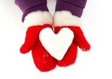 Cuore di Snowy in mani con i guanti rossi fotografia stock libera da diritti