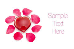 Cuore di vetro con i petali di rosa Fotografia Stock